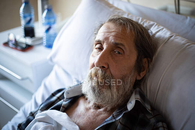 Calm aged man with beard lying under blanket on bed in hospital ward looking at camera — Stock Photo