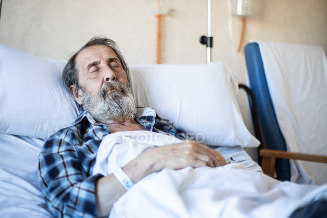 Calm aged man with beard lying under blanket on bed in hospital ward and sleeping — Stock Photo
