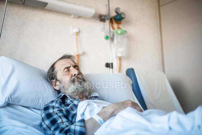 Hombre de edad calma con barba acostado debajo de la manta en la cama en la sala de hospital y durmiendo - foto de stock