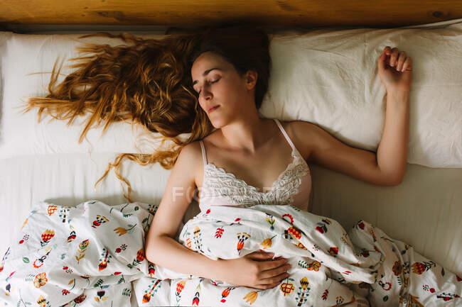 Von oben sieht man eine junge, gelassene Frau mit langen welligen Haaren, die einen SpitzenbH trägt und in einem gemütlichen Bett mit weißen Laken und Zierdecke schläft — Stockfoto