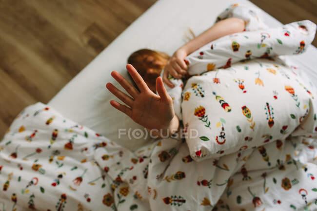 De cima anônimo jovem fêmea em cueca levantando braço para cima escondendo o rosto da câmera enquanto deitado na cama logo após acordar de manhã — Fotografia de Stock