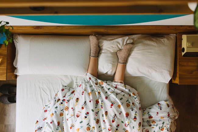 Сверху неизвестная женщина в носках, лежащих в постели, покрытая одеялом с ногами на подушках — стоковое фото