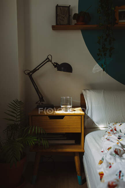 Glass of water in sunlight placed on wooden bed table with lamp near unmade bed in cozy bedroom in morning — Stock Photo