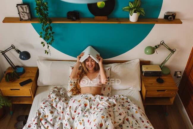 Dall'alto di giovane femmina allegra con occhi chiusi che giace in libro di tenuta di letto comodo sopra la testa di mattina alla camera da letto — Foto stock