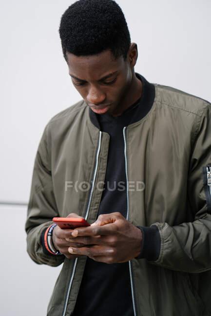 Молодий афроамериканець у повсякденному одязі стоїть навпроти сірої стіни і пише смартфон на вулицях міста. — стокове фото