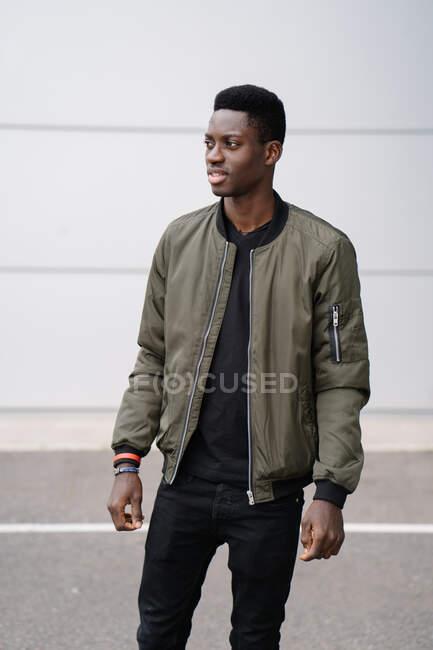 Relaxed black man on modern city street — Stock Photo