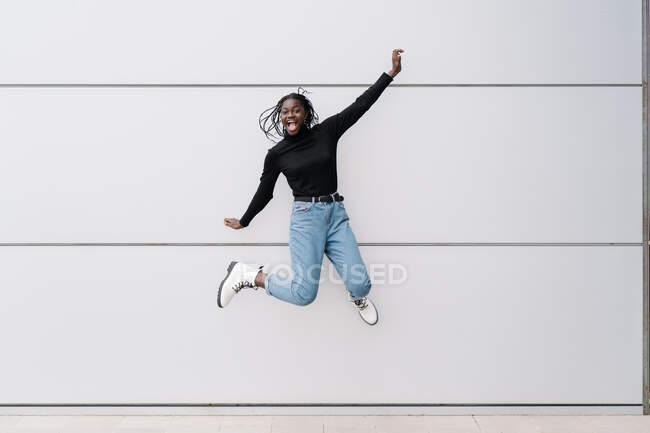 Corpo inteiro encantado mulher negra em roupas casuais gritando e pulando contra a parede do edifício cinza na rua da cidade contemporânea — Fotografia de Stock