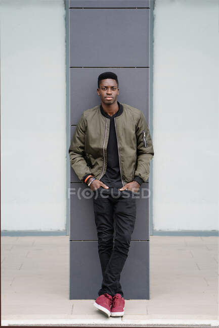 Full body confident African American man with hands in pockets leaning on column and looking at camera while spending time on contemporary city street — Stock Photo