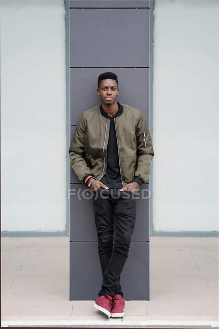 Hombre afroamericano seguro de cuerpo completo con las manos en los bolsillos apoyados en la columna y mirando a la cámara mientras pasa tiempo en la calle contemporánea de la ciudad - foto de stock