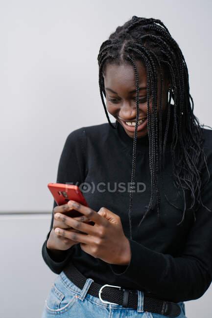 Allegro giovane ragazza nera in abiti casual sorridente e sms messaggio sullo smartphone mentre in piedi vicino al muro grigio di edificio moderno sulla strada della città — Foto stock