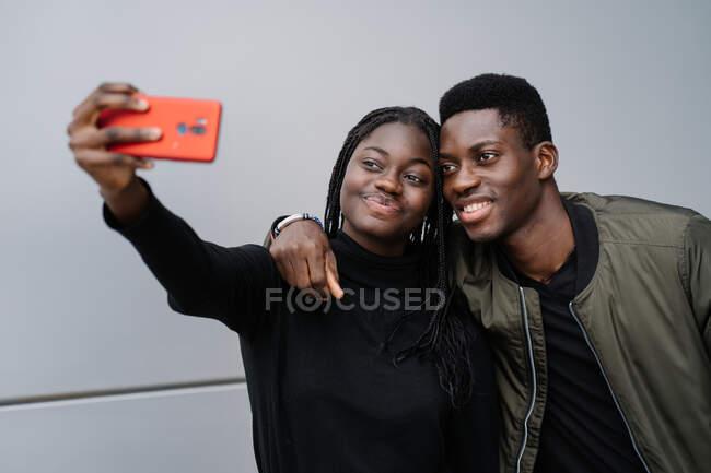 Cheerful black couple taking selfie on street — Stock Photo