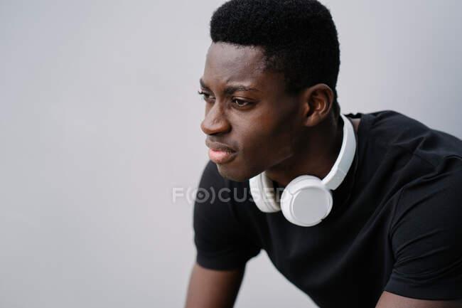 Insatisfeito afro-americano cara com fones de ouvido brancos franzindo a testa e olhando para longe enquanto sentado contra fundo cinza na rua da cidade — Fotografia de Stock