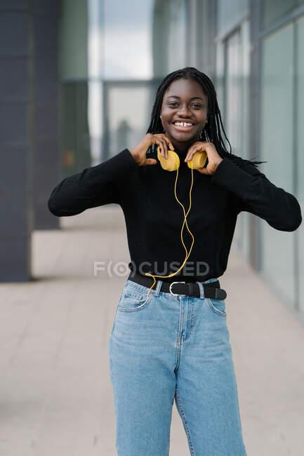 Mulher negra com fones de ouvido na rua — Fotografia de Stock