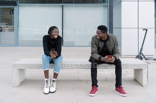 Ganzkörperjunge afroamerikanische Männer und Frauen mit Smartphones lächeln und schauen einander an, während sie auf einer Bank sitzen und Bekanntschaft auf der modernen Stadtstraße machen. — Stockfoto