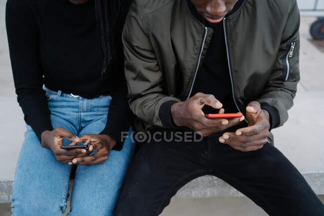 D'en haut noir homme et femme en vêtements décontractés assis sur le banc et la navigation smartphones pendant la date sur la rue de la ville — Photo de stock