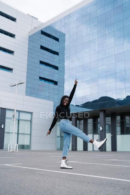 Felice donna afroamericana che salta contro il muro — Foto stock