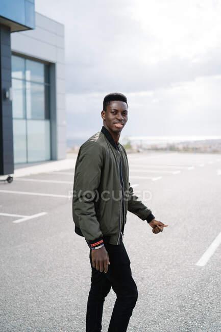 Красивый афроамериканец в повседневной одежде смотрит в камеру, когда идет по асфальтовой парковке на фоне облачного неба на городской улице — стоковое фото