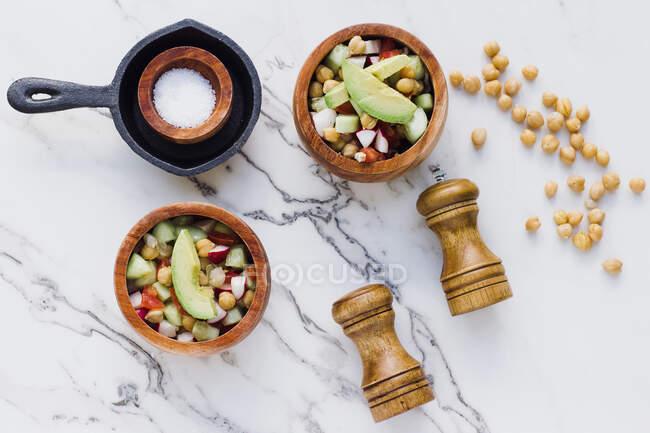 Flache hölzerne Schalen mit Avocadosalat mit Kichererbsen auf weißem Marmortisch mit Salz-Pfeffer-Gewürzen — Stockfoto
