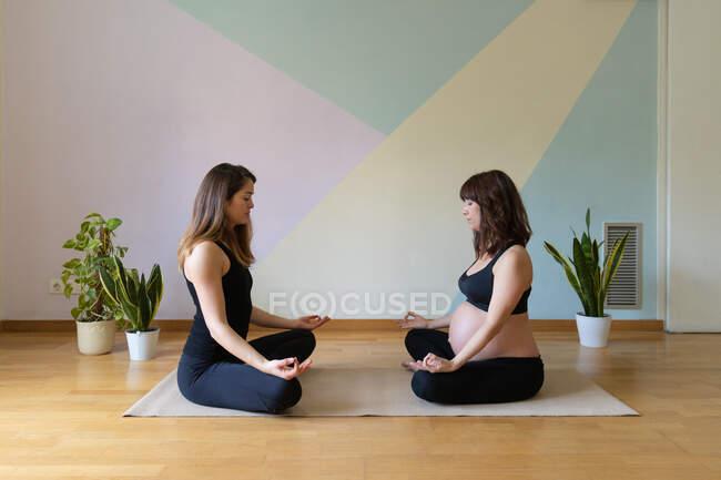 Все тело беременной женщины с тренером, сидящей на полу в позе лотоса и медитирующей вместе во время тренировки йоги в студии — стоковое фото