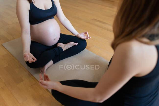 Обрезанная неузнаваемая беременная женщина-тренер, сидящая на полу в позе лотоса и медитирующая вместе во время тренировки йоги в студии — стоковое фото