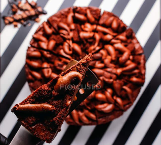 Vista aérea de pastel de chocolate dulce entero con barra de chocolate en la superficie a rayas en blanco y negro - foto de stock