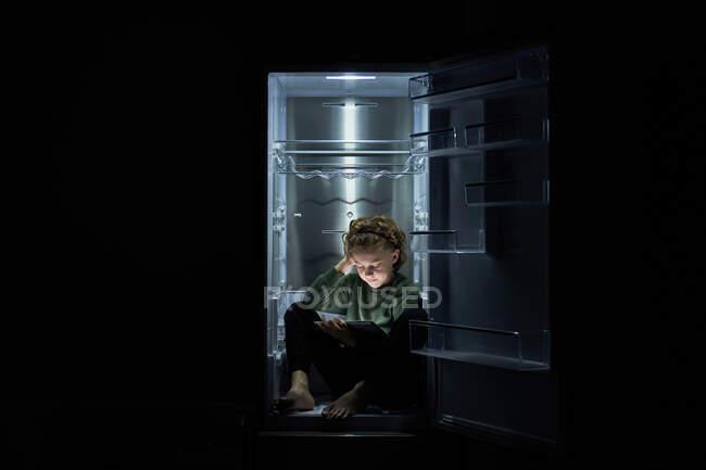 Спокійна розслаблена дитина сидить у порожньому холодильнику і користується цифровим планшетом у гарячу ніч. — стокове фото