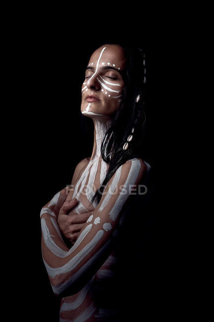 Side view of naked tender beautiful brunette Native American woman with white striped painted on body covering breast standing in dark on black background — Stock Photo