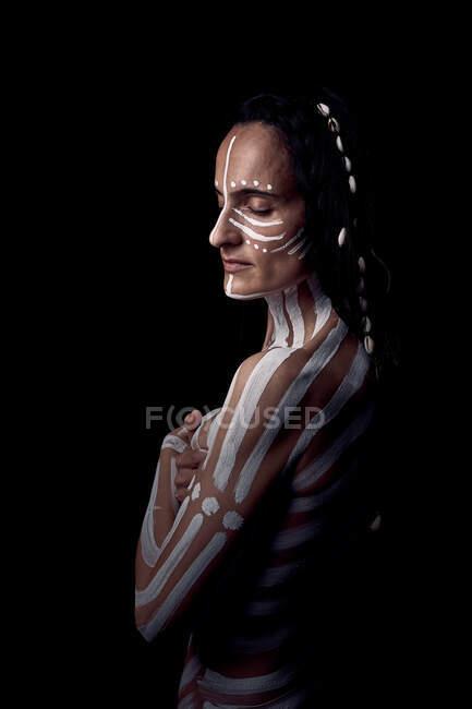 Lato vista di nudo tenero bella bruna nativo americano donna con bianco a righe dipinta su corpo coprendo seno in piedi al buio su sfondo nero — Foto stock