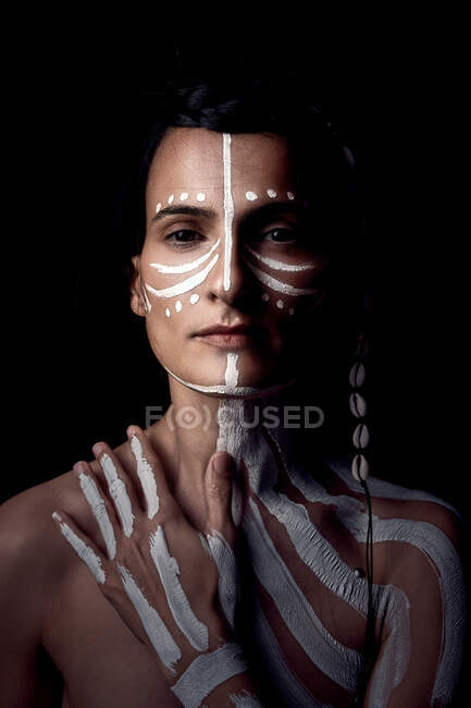 Portrait of naked tender beautiful brunette Native American woman with white striped painted on body covering breast standing in dark on black background looking at camera — Stock Photo