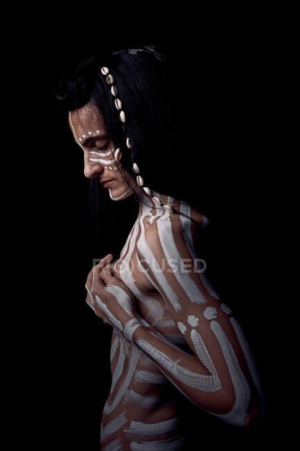Vista laterale di nudo tenera bella bruna Native American donna con strisce bianche dipinte sul corpo che copre il seno in piedi nel buio su sfondo nero — Foto stock