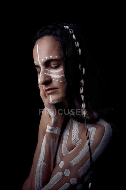 Vue de côté portrait de nue tendre belle brune amérindienne avec rayures blanches peintes sur le corps couvrant poitrine debout dans l'obscurité sur fond noir avec les yeux fermés — Photo de stock