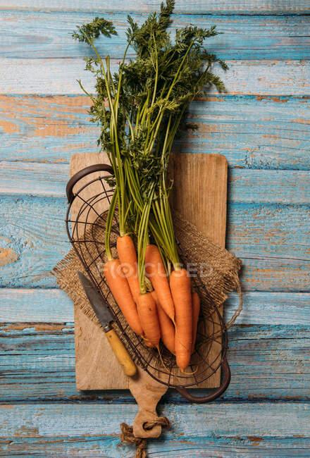 Vista superior de zanahorias maduras cosechadas con follaje verde colocado en la tabla de cortar en la mesa de madera - foto de stock
