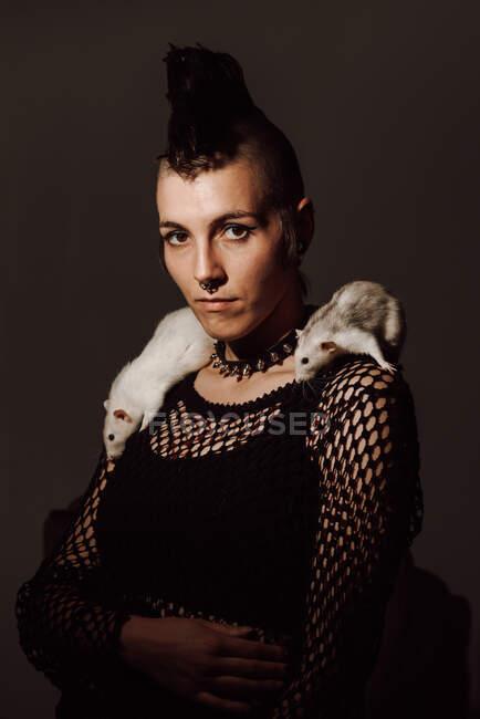 Впевнена жінка з білою пацючкою на плечах і дивиться на камеру на чорному тлі. — стокове фото