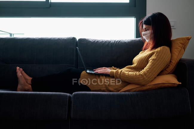 Женщина, работающая с ноутбуком дома в облачный день с маской на диване во время вспышки коронавируса — стоковое фото