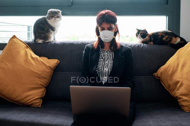 Frau arbeitet zu Hause mit Laptop und Maske auf dem Sofa an einem bewölkten Tag während des Coronavirus-Ausbruchs — Stockfoto
