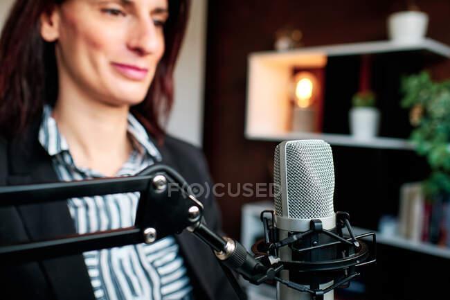 Una mujer de negocios preparada para podcast con micrófono - foto de stock