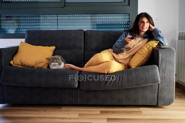 Jeune femme sur son canapé avec chat exotique en utilisant la télécommande tandis qu'à la maison par le virus de la couronne — Photo de stock