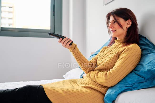 Frau auf ihrem Bett bei Ausbruch des Coronavirus mit der Fernbedienung — Stockfoto