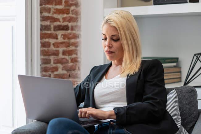 Веселая блондинка-бизнесмен улыбается и просматривает ноутбук, сидя в удобном кресле рядом с камином в уютной комнате, работая удаленно от дома — стоковое фото