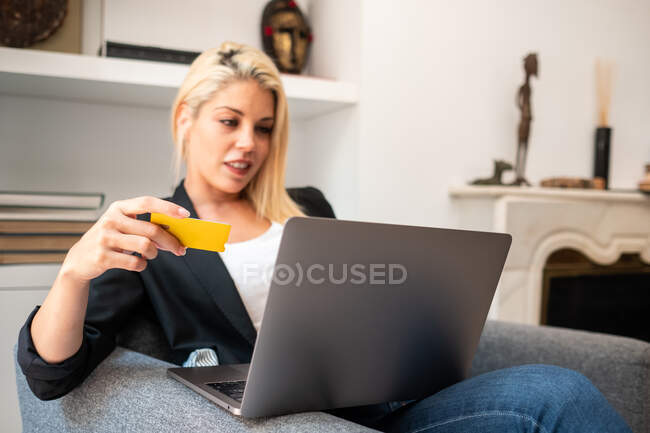 Blonde female in casual clothes entering credit card credentials on laptop while sitting in comfortable armchair and making online purchases at home — Stock Photo