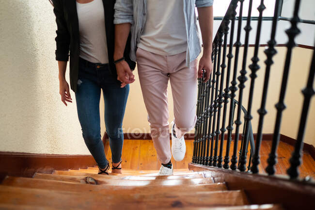 From above anonymous man and woman in casual clothes holding hands and walking up steps at home — Stock Photo