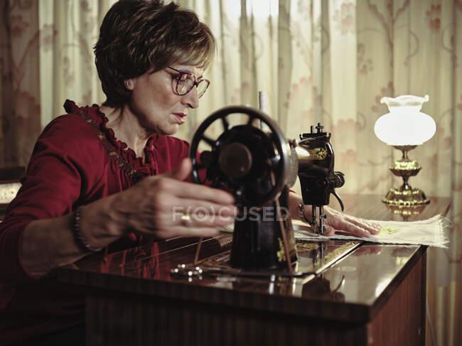 Старша жінка в окулярах, використовуючи ретро швейну машину, щоб створити білизну серветки в затишній кімнаті вдома — стокове фото