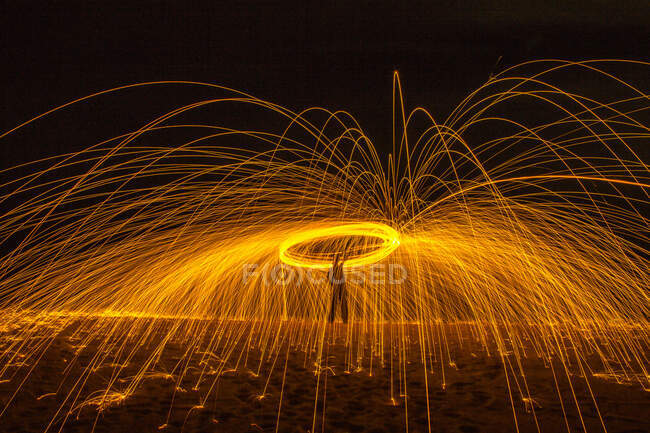 Long exposure silhouette of unrecognizable person spinning burning stick emitting sparkles while dancing with fire at night — Stock Photo