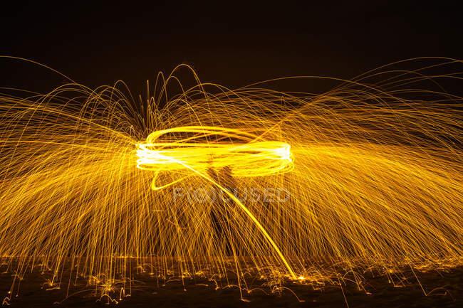 Довгочасний силует непізнаної людини, що крутить палаючу палицю, випромінюючи блискітки під час танців з вогнем вночі. — стокове фото