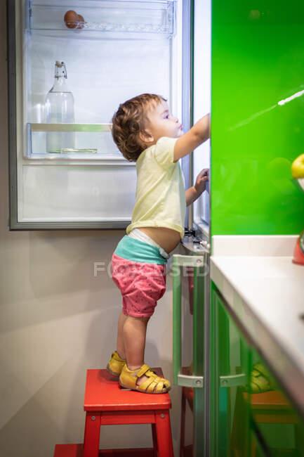 Вид сбоку симпатичного маленького ребенка, стоящего на табуретке и принимающего еду из открытого холодильника на уютной домашней кухне — стоковое фото
