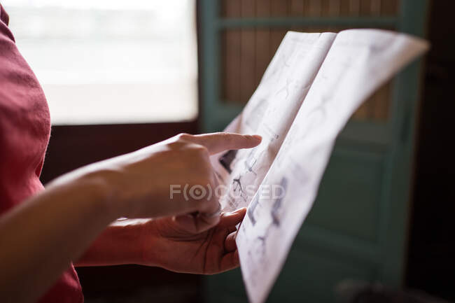 Unrecognizable woman pointing at paper sheet and reading manual before assembling furniture at home — Stock Photo