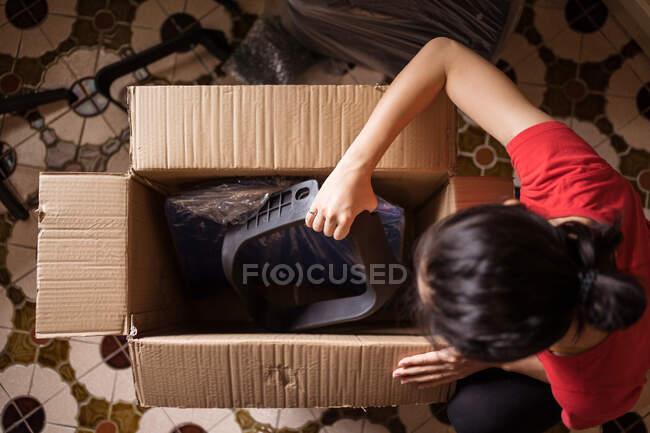 Vista dall'alto di donne anonime che prendono parti di sedia dalla scatola di cartone prima di assemblare mobili a casa — Foto stock