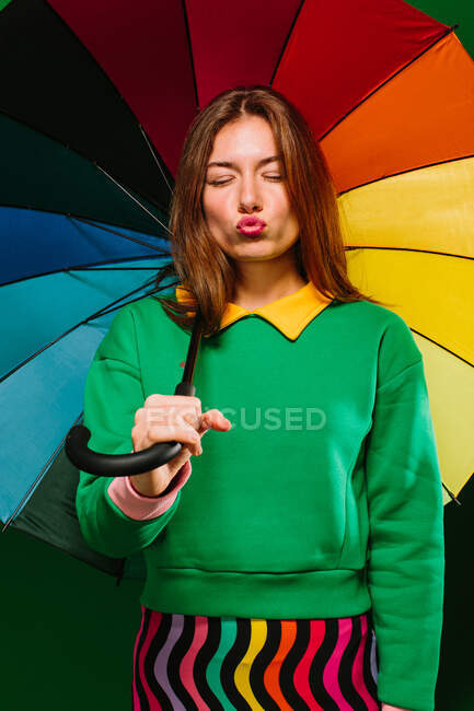 Young blonde female model in colorful outfit holding multicolored umbrella grimacing with closed eyes while standing against green background — Stock Photo