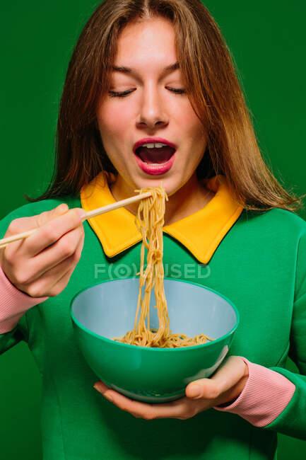Позитивная молодая женщина в зеленой рубашке с закрытыми глазами, открывая рот, чтобы съесть вкусную лапшу с палочками на зеленом фоне — стоковое фото