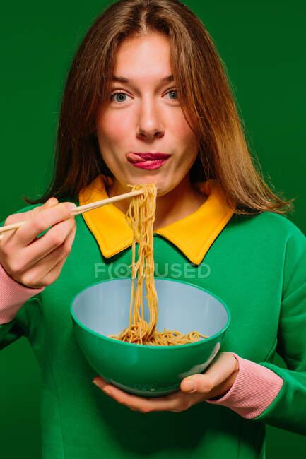 Позитивная молодая женщина в зеленой рубашке смотрит на камеру гримаса высовывая язык во время еды вкусной лапши с палочками на зеленом фоне — стоковое фото